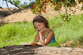 young girl reading under a tree