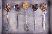 Seasonings in metal spoons on wooden background