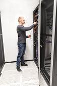 IT consultant installs network rack in datacenter