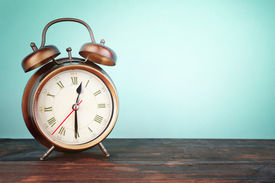 foto of countdown  - Old alarm clock on wooden table on blue background - JPG
