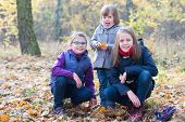pic of three sisters  - Three sisters in the autumnal forest smiling and hugging - JPG