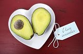 picture of wood pieces  - Avocado cut in half on heart shape plate on dark red vintage rustic wood table with I Love Avocados text sign - JPG
