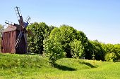 Ancient Windmill On A Hill In A Field. Against The Background Of Green Grass. Historic Site.