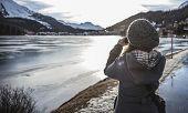 Woman Takes A Picture Of A Frozen Lake