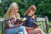 Two girls reading books on bench in nature