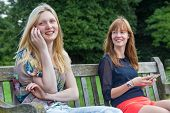 Two girls sitting on bench in park with mobile phones