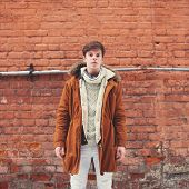 Fashion Man Outdoors In Urban Style On Against A Brick Wall