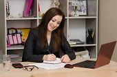 Female Office Worker Grinning Writing In A Notebook For Your Desktop