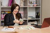 Girl Behind Desk In Office Feverishly Counts Banknotes With A Triumphant Smile