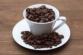 Cup with coffee beans on wood