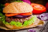 Homemade Hamburger With Fresh Green Lettuce, Tomatoes And Red Onions Closeup