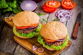 Homemade Burgers With Fresh Organic Vegetables On A Rustic Background