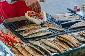 foto of saltwater fish  - Men selling fish in bread on grill - JPG