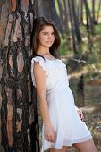 Beautiful Young Woman In White Dress Standing In The Forest