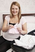 Pregnant Woman Packing Suitcase For Trip To Hospital
