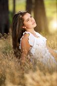 Attractive Girl Sitting In Meadow With White Dress