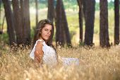 Sensual Young Woman Sitting In A Field In Nature