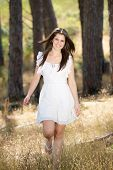 Happy Young Woman In White Dress Walking In Nature