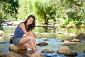 Happy Young Woman Sitting By Stream With Feet In Water