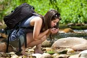 Female Hiker With Backpack Drinking Water From Stream In Nature