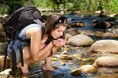 Woman Hiker With Bag Drinking Water From Stream In Nature