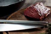 Tenderloin fillet lying on wooden board with a knife and steel
