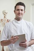 Portrait Of Osteopath In Consulting Room With Digital Tablet