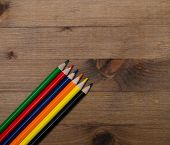 set of multicolored pencils on   wooden table