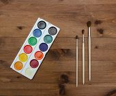 palette with paint and brushes on  wooden table