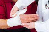 foto of bandage  - Photo of doctor bandaging the elderly woman thumb - JPG