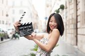 Young Asian Woman Smiling And Shows Clapperboard Urban Scene