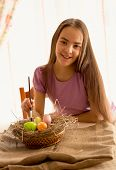 Cute Smiling Girl Sitting At Table With Easter Eggs