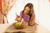 Cute Girl Decorating Easter Eggs In Basket