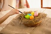 Closeup Shot Of Girl Holding Paintbrush Coloring Easter Eggs