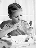 Monochrome Portrait Of Cute Girl Painting Easter Egg