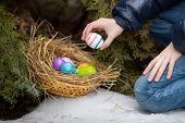 Little Girl Putting Easter Egg In Nest At Cold Snowy Day
