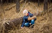 Little Girl Looking For Easter Eggs Under Log At Forest