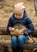 Girl In Forest Looking At Colored Easter Eggs In Basket