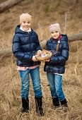 Two Girls On Easter Egg Hunt At Forest