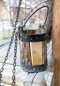 stock photo of groundwater  - Detail of old draw well with wooden bucket on a metal chain close up view in Izmailovo Kremlin Moscow Russia - JPG