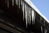 Iicicles On A House Roof Thaw On The Sun