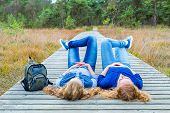 Two girls lying on their backs on wooden path in nature