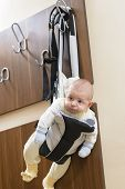 picture of laughable  - Cute baby sitting in a front baby carrier - JPG