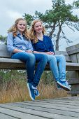 Two girls sitting on wooden bench in nature