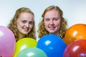 Two girls heads behind colored balloons