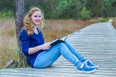 Girl reading book on wooden path in nature
