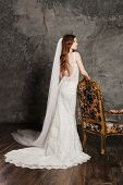 Back view of a beautiful sexy bride in luxurious wedding dress into elegant expensive interior