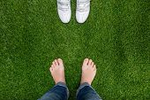 Feet Resting On Grass With Sneakers Standing Opposit