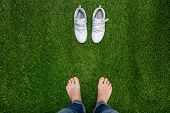 Feet Resting On Green Grass With Sneakers Standing Opposit