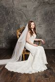 Photo of a beautiful smiling bride in luxurious wedding dress into elegant expensive interior